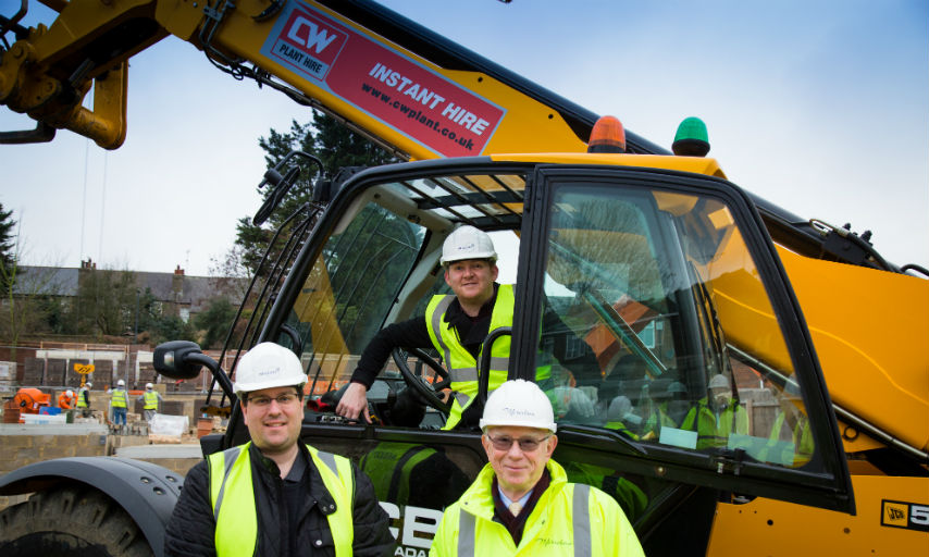 Councillor Thorpe, Councillor Kirby & Richard Reynolds from Meridian Home Start pictured around a yellow tractor at Woodpecker Gardens construction site