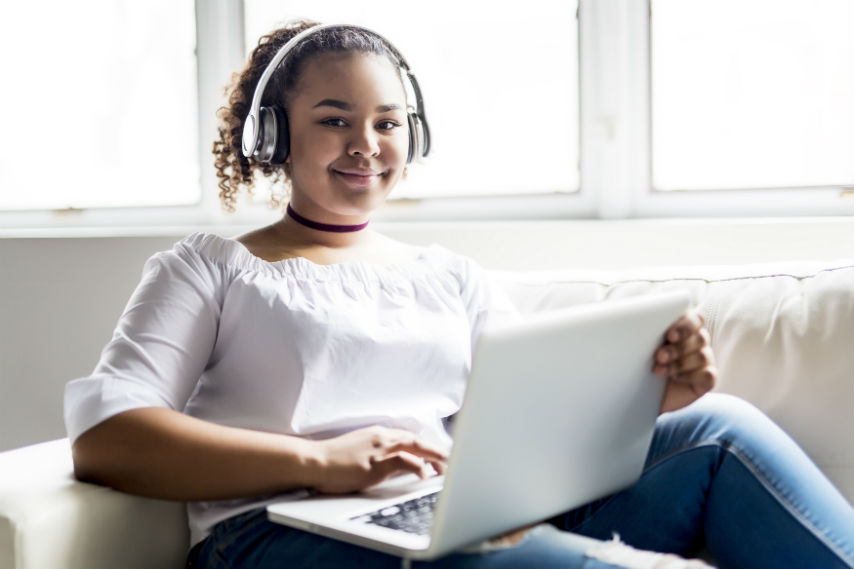 Smiling teenage girl with silver headphones on, sitting on a cream sofa, holding a white laptop.