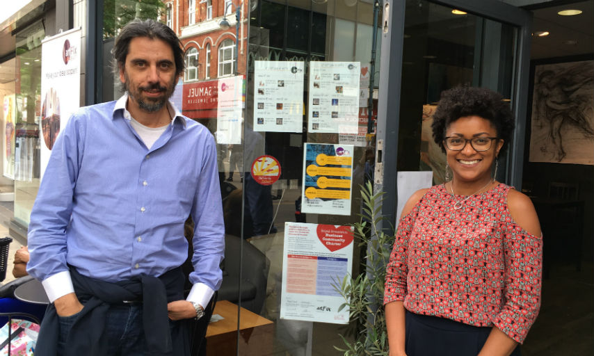 A white man in a blue shirt standing next to a smiling black woman who's wearing black glasses and a red blouse. They are both standing outside the artFix cafe in Woolwich.