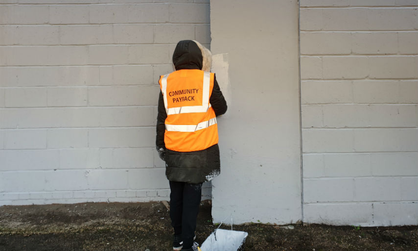 Community payback service user painting a wall.